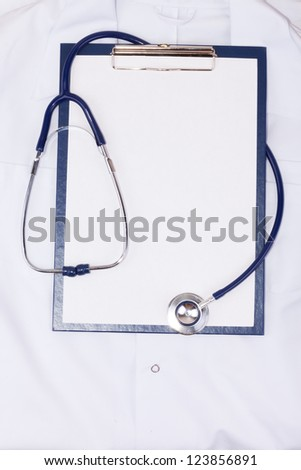 Medical clipboard and stethoscope on medical gown - stock photo