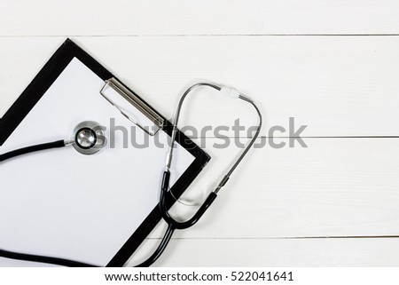 Medical clipboard and stethoscope on white wooden table background. Top view. Health care and medicine concept.