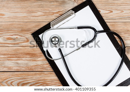 Medical clipboard and stethoscope on wooden table background. Top view. Health care and medicine concept.