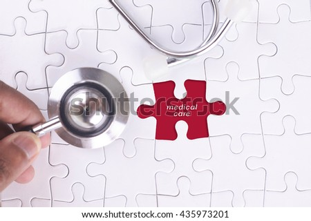 Medical Concept - A doctor holding a Stethoscope on missing puzzle with medical care WORD - stock photo