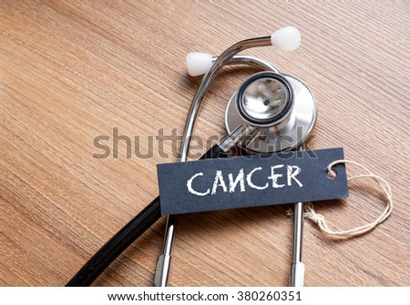 Medical Concept-cancer word written on label tag with Stethoscope on wood background - stock photo