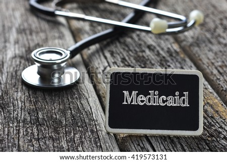 Medical Concept- Medicaid word written on blackboard with Stethoscope on wood background - stock photo