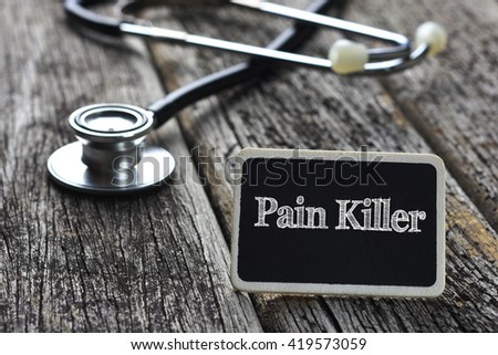 Medical Concept-Pain Killer word written on blackboard with Stethoscope on wood background - stock photo