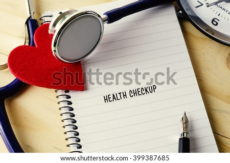 Medical concept. Stethoscope, heart shape, notepad, clock and pen on wooden table with HEALTH CHECKUP words. - stock photo