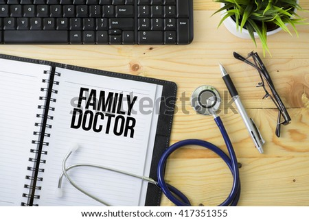 Medical Concept - Stethoscope with notebook written Family Doctor with keyboard, green plant, a pen and spectacle on wooden background - stock photo