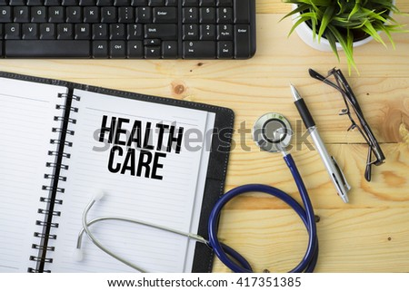 Medical Concept - Stethoscope with notebook written Health Care with keyboard, green plant, a pen and spectacle on wooden background - stock photo