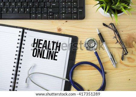 Medical Concept - Stethoscope with notebook written Health Online with keyboard, green plant, a pen and spectacle on wooden background - stock photo