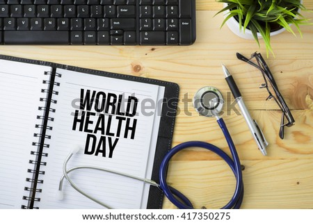 Medical Concept - Stethoscope with notebook written World Health Day with keyboard, green plant, a pen and spectacle on wooden background - stock photo