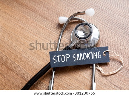 Medical Concept-Stop Smoking word written on label tag with Stethoscope on wood background - stock photo