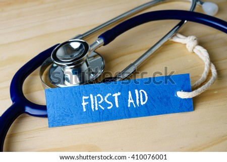 Medical conceptual image with FIRST AID words and stethoscope on wooden background. - stock photo