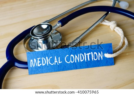 Medical conceptual image with MEDICAL CONDITION words and stethoscope on wooden background. - stock photo