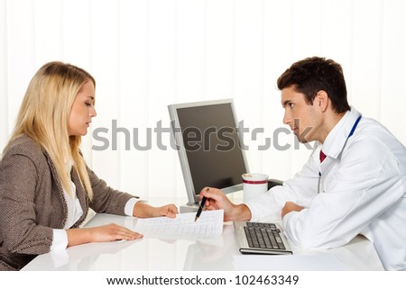 medical consultation. patient and doctor talking to a doctor's office - stock photo