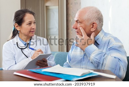 Medical consultation. Senior patient and doctor talking at table - stock photo