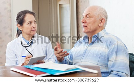 Medical consultation. Senior patient and doctor talking at table with documents