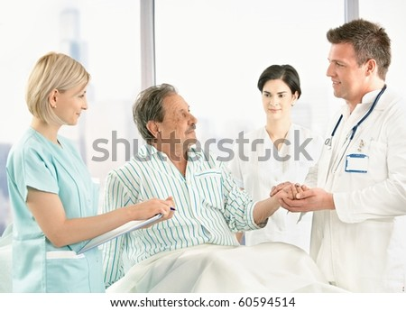 Medical crew talking to old patient in hospital, doctor holding his hand.?