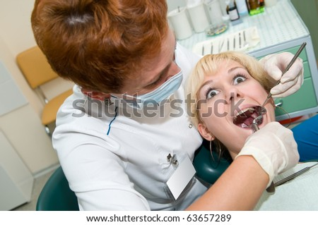 medical dental teeth surgery procedure exodontia at clinic with scared patient - stock photo