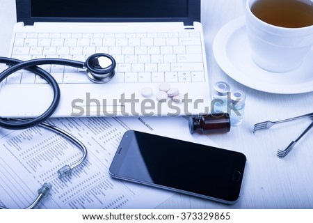 medical devices on the table at the doctor on a light background with wooden texture with blue toned - stock photo