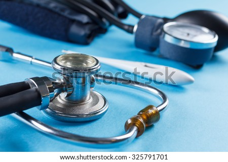 Medical devices stethoscope, tonometer, and thermometer on blue background - stock photo