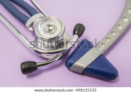 Medical diagnostic tools for neurologist or doctor of internal medicine. Stethoscope or phonendoscope with blue neurological reflex hammer lying on purple background or table in doctor's office