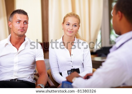 Medical doctor and young couple patients having a conversation in the hospital - stock photo
