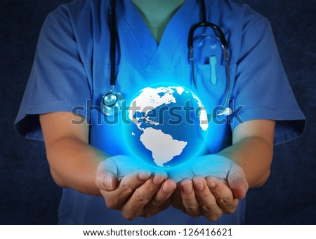 Medical Doctor holding a world globe in his hands as medical network concept - stock photo