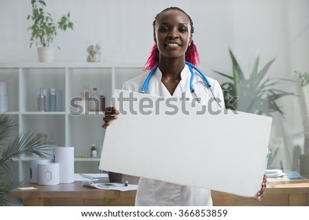 Medical doctor holding banner at her office - stock photo