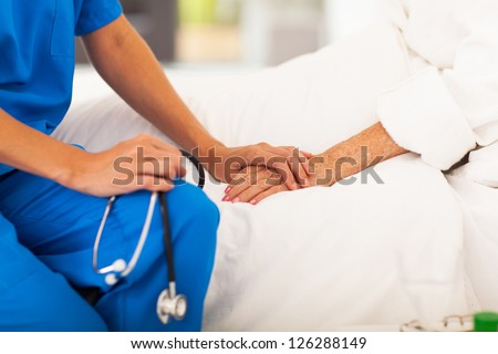 medical doctor holing senior patient's hands and comforting her - stock photo