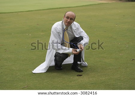 Medical doctor on the golf course checking a golf ball with his stethoscope, in the hope of helping you improve your game - stock photo