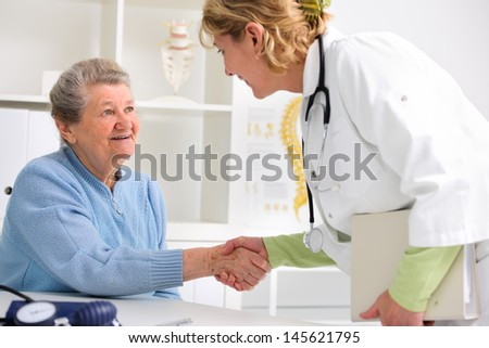 medical doctor shaking hands to happy senior patient