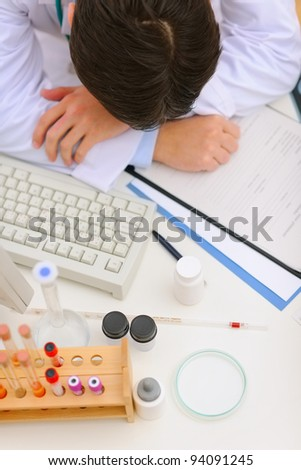 Medical doctor sleeping on desk with medical stuff. Top view - stock photo