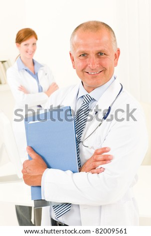 Medical doctor team senior man with female nurse holding folders