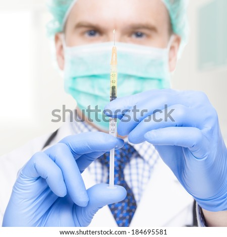Medical doctor with a syringe in his hand - 1 to 1 ratio - stock photo