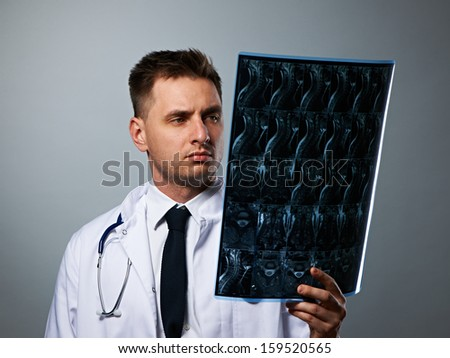 Medical doctor with MRI spinal scan portrait against grey background  - stock photo