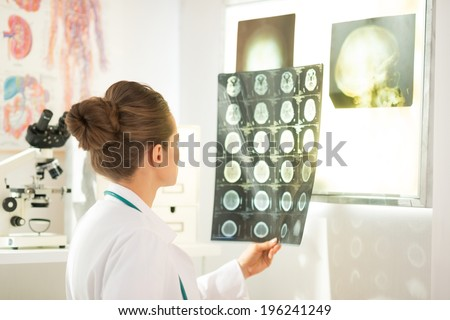 Medical doctor woman looking on tomography - stock photo