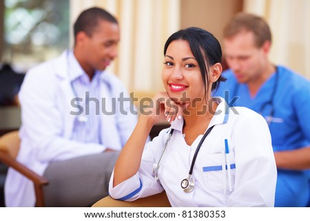 Medical doctor woman smiling indoors with her colleagues working behind
