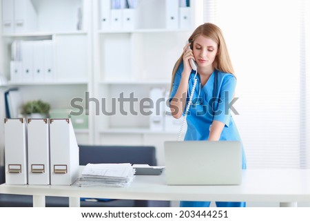 Medical doctor woman with computer and telephone. - stock photo