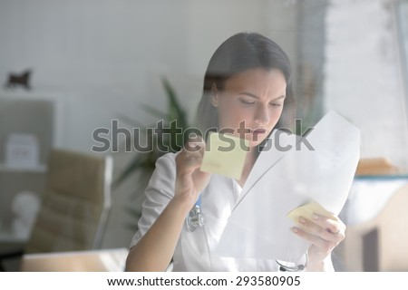 Medical doctor writing patient test results on transparent board to diagnose  - stock photo