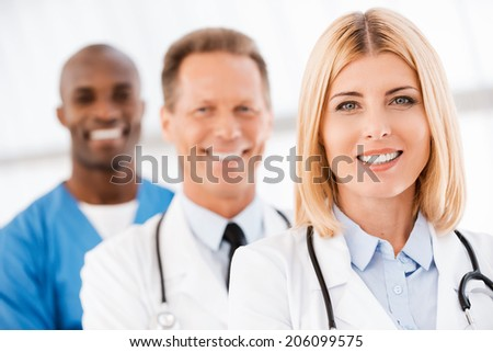 Medical doctors team. Confident female doctor looking at camera and smiling while her colleagues standing in a row behind her - stock photo