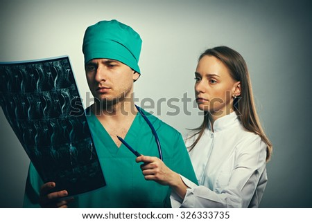 Medical doctors team with MRI spinal scan portrait against grey background  - stock photo