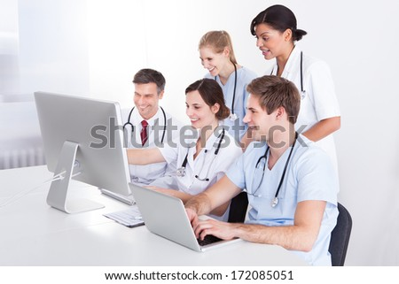 Medical Doctors Working On Computer And Laptop In Hospital - stock photo