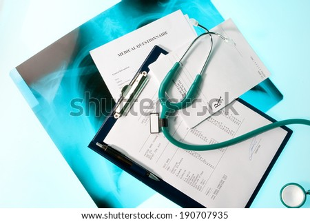 Medical documents (blood test, prescription and medical questionnaire) with a stethoscope on Xray photo of lungs - stock photo