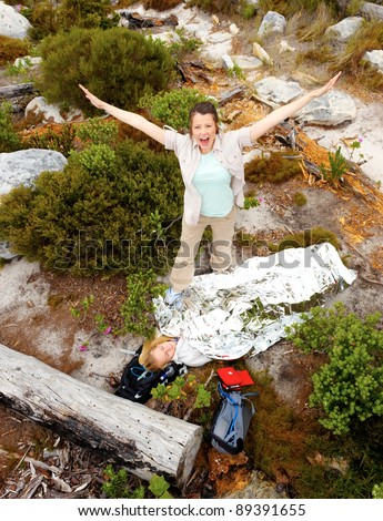 Medical emergency while hiking. woman has emergency blanket and her friend is calling for help - stock photo