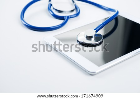 Medical equipment: blue stethoscope and tablet on white background. - stock photo