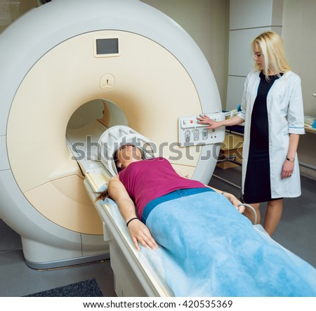 Medical equipment. Doctor and patient in MRI room at hospital.