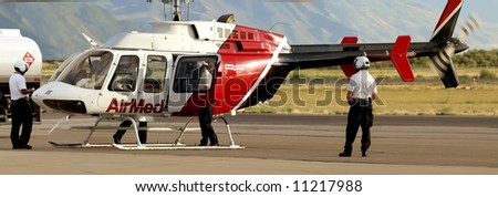 Medical evacuation helicopter and crewmen at airport - stock photo