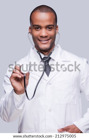 Medical exam. Confident African doctor stretching out his stethoscope and smiling while standing against grey background - stock photo