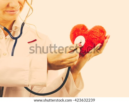 Medical examination of cardiology. Cardiologist with heart and stethoscope. Female doctor in white uniform makes measurement heartbeat. Filtered. - stock photo