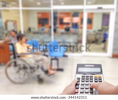 Medical expense concept by the calculator with blur patient at the hospital in background - stock photo