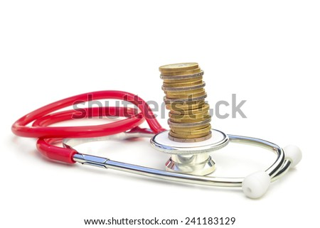 Medical expenses 4.  --  A stethoscope with a pile of coins on top. - stock photo