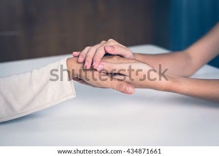 Medical female doctor's hands holding patient's hand for encouragement and empathy at a hospital or clinic patient cheering and support. Keeping good health concept, To build strength Body and mind. - stock photo